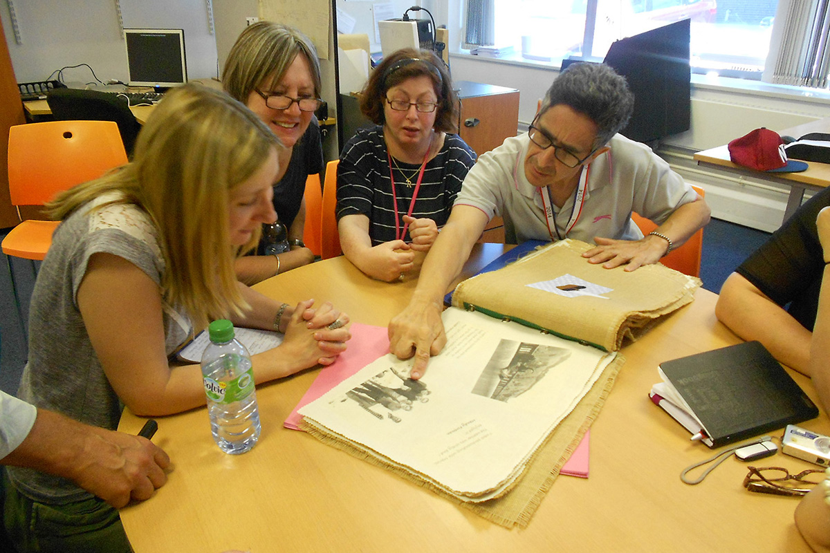 Group of people looking at a scrapbook