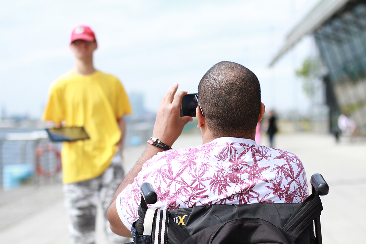 Young person in wheelchair takes photo of friend