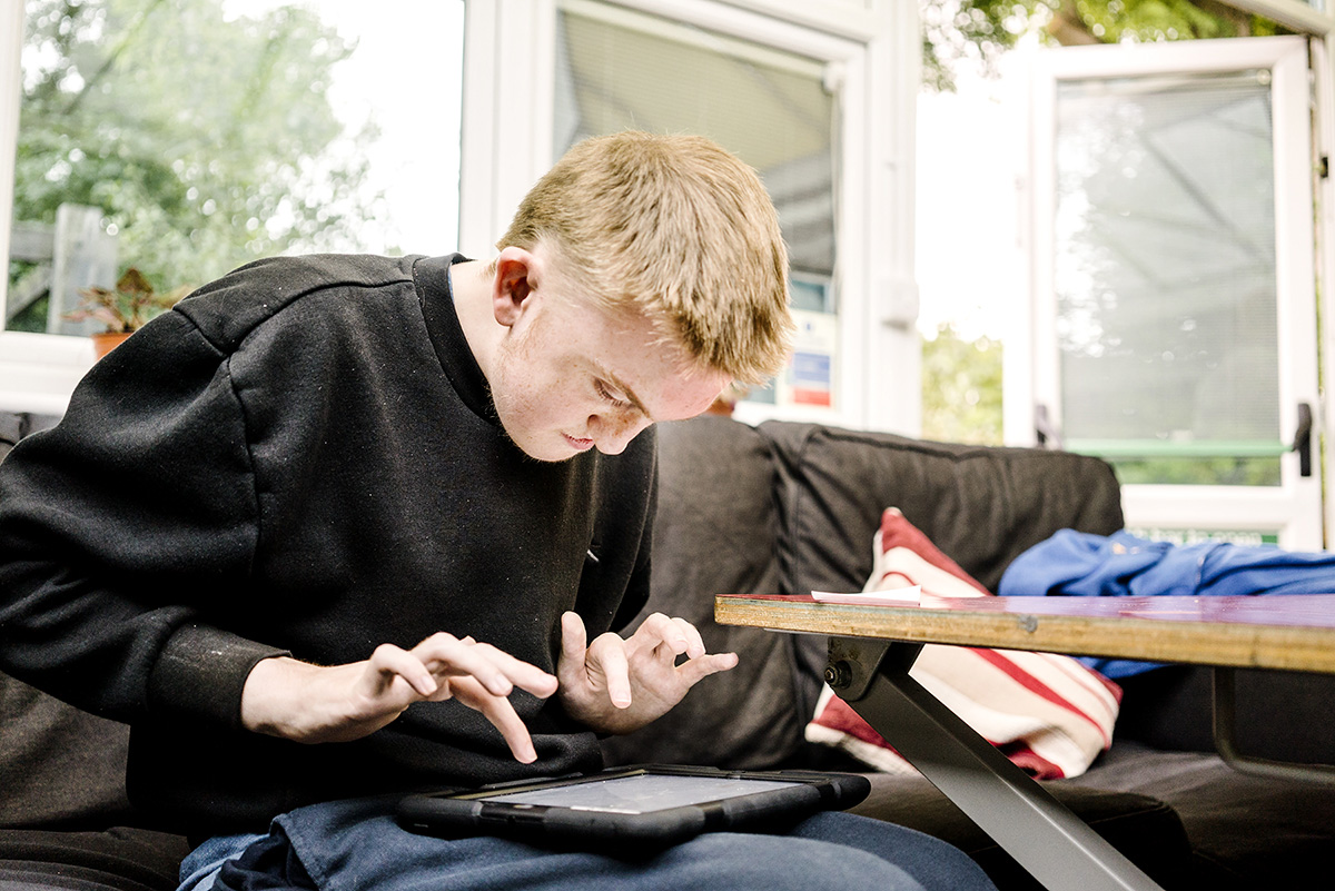 Young person typing on tablet