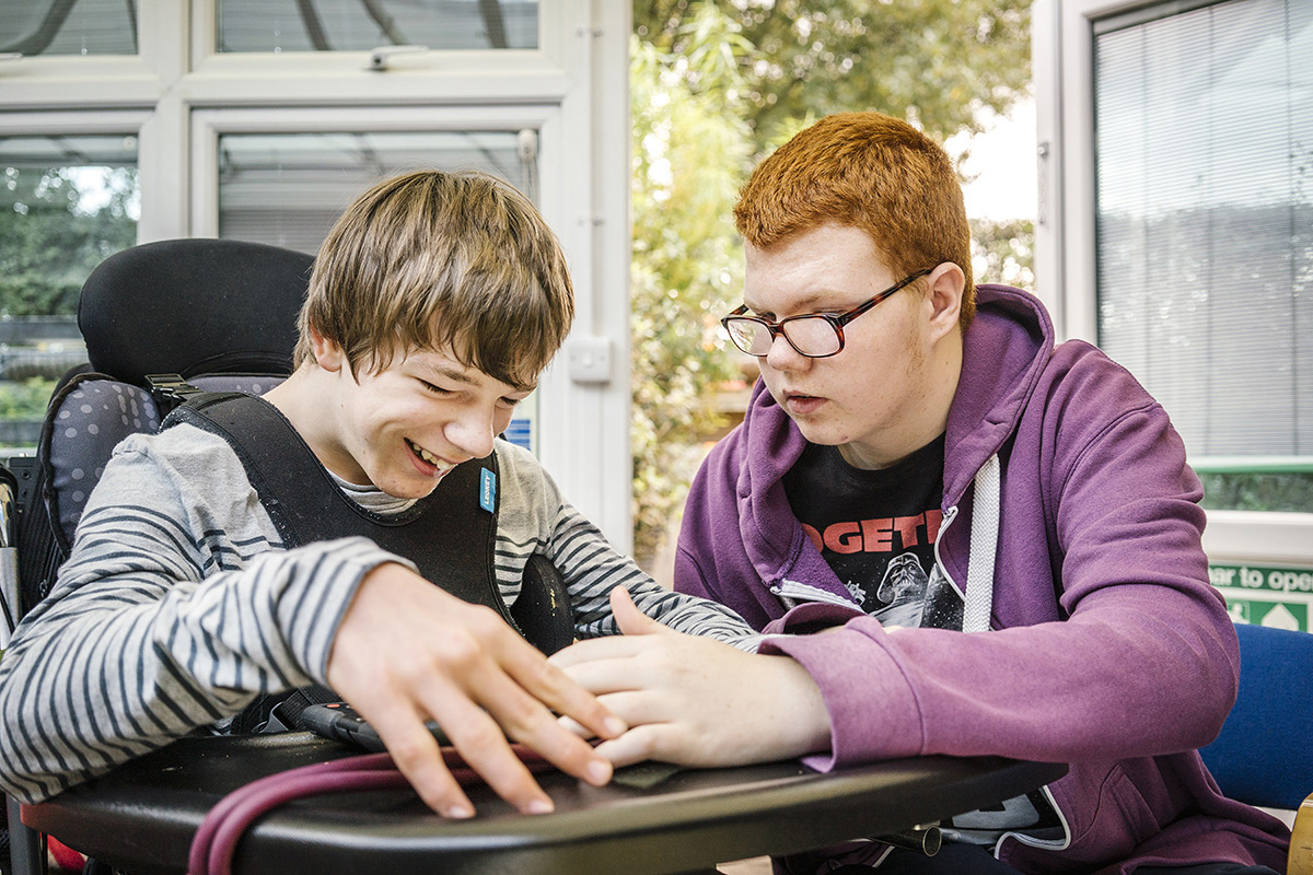 Young person looks at Wiki with young person in wheelchair
